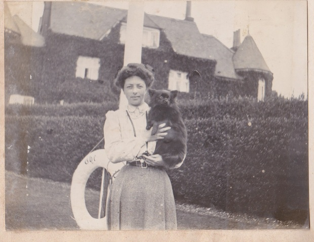 Kate with Mickie. Photographed on the riverside at Bourne End, with The Plat, which until 1913 was her home, in the background